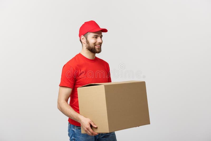 Homem de entrega logístico de sorriso dos jovens no uniforme vermelho que guarda a caixa no fundo branco fotografia de stock
