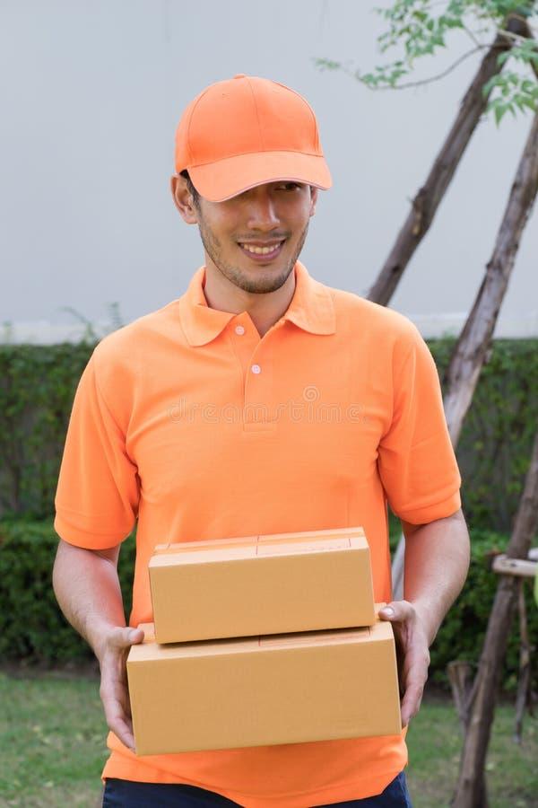Homem de entrega no pacote trazendo alaranjado imagens de stock