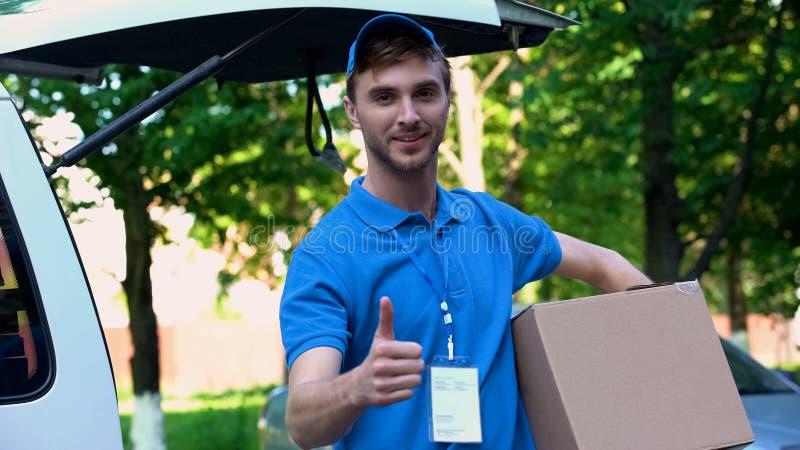 Homem de entrega novo que guarda o pacote, mostrando os polegares acima, serviço de transporte rápido imagens de stock royalty free