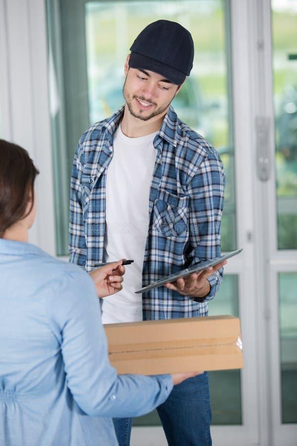 Homem de entrega novo de sorriso que guarda a caixa de cartão fotografia de stock royalty free