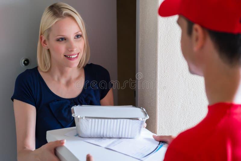 Homem de entrega que dá a ordem do fast food ao cliente imagens de stock royalty free