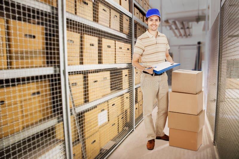 Homem de entrega que guarda a prancheta por caixas de cartão no armazém fotos de stock royalty free