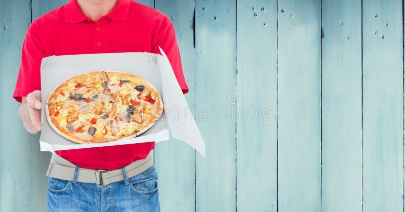 Homem de entrega que mantém a caixa da pizza contra o fundo de madeira fotos de stock royalty free