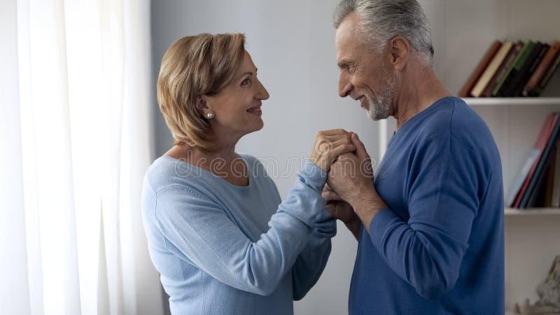 Homem de envelhecimento que guarda as mãos das senhoras, preparando-se para beijá-los, senhora que é tímida, coquete fotografia de stock