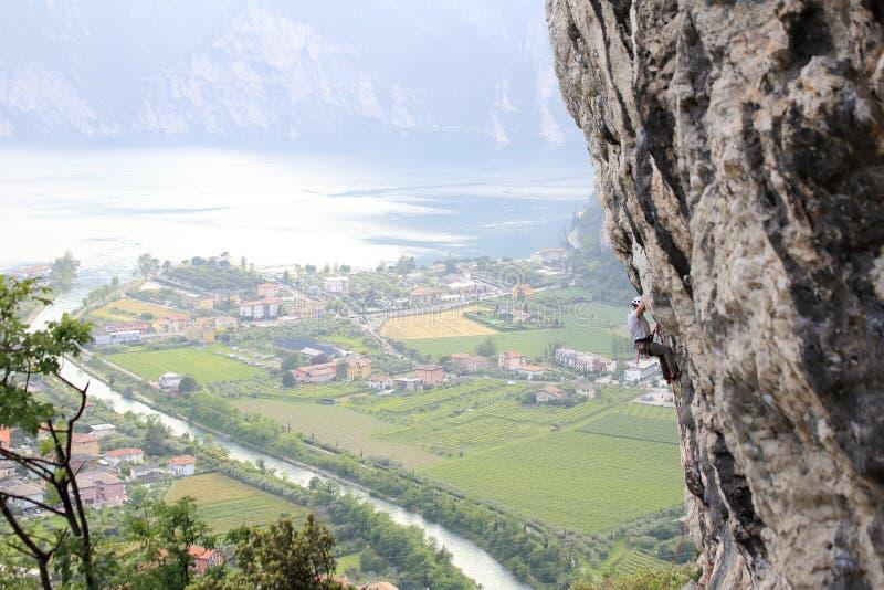 Homem de escalada em uma parede da rocha imagem de stock
