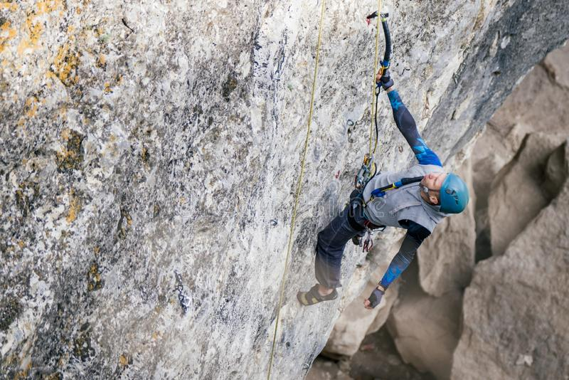 Homem de escalada em uma rocha fotografia de stock royalty free