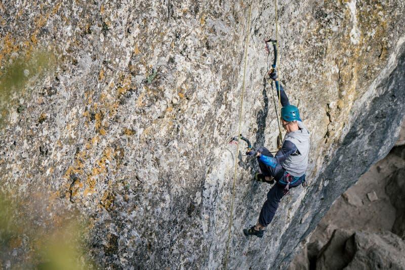 Homem de escalada em uma rocha imagens de stock royalty free