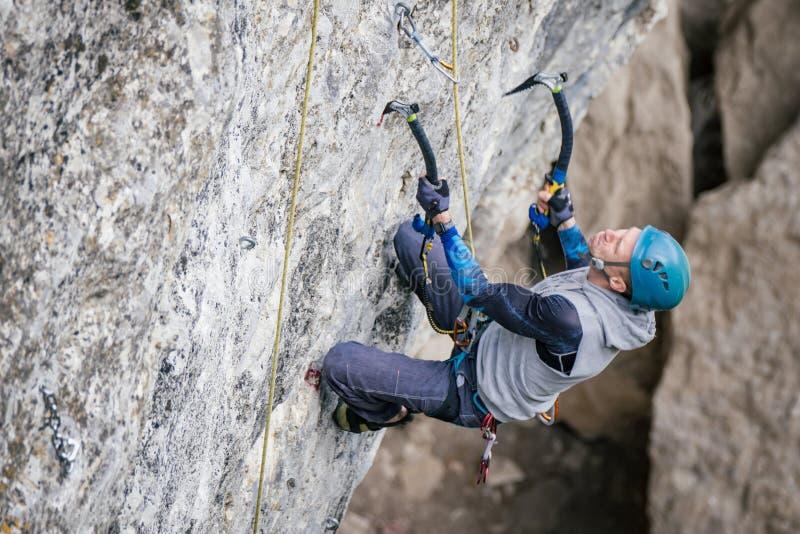 Homem de escalada em uma rocha fotografia de stock