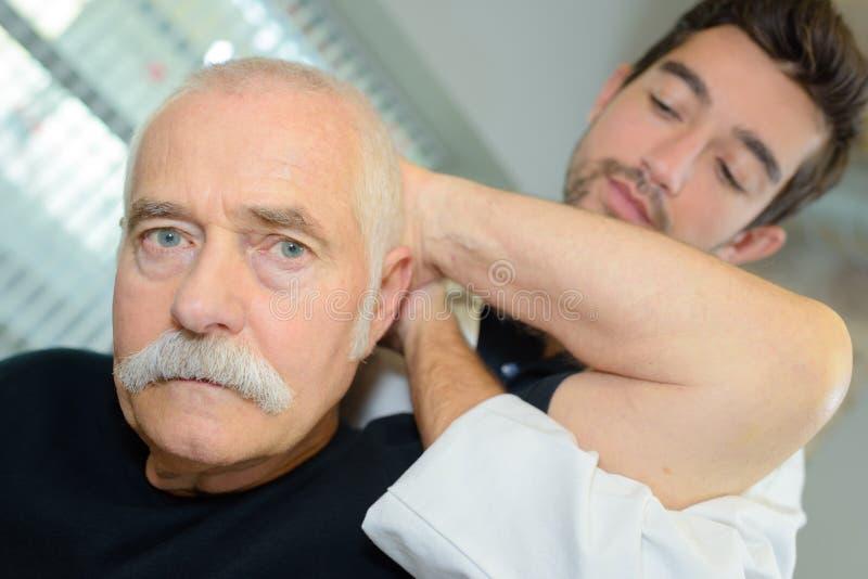 Homem de exame das pessoas idosas do pescoço do fisioterapeuta masculino imagem de stock royalty free