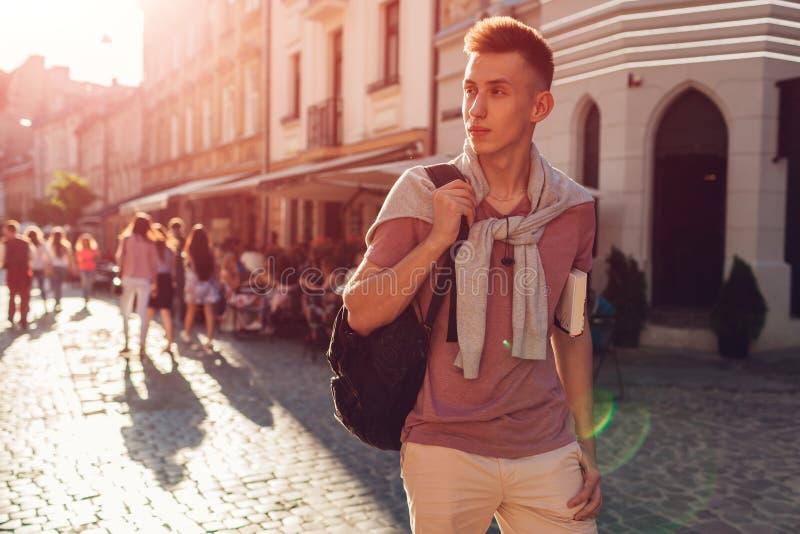 Homem de faculdade considerável que anda na rua da cidade Estudante feliz do indivíduo com a trouxa que guarda um livro fotos de stock
