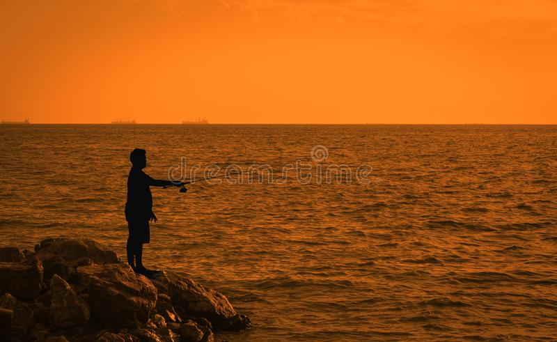 Homem de Fisher que pesca com haste de gerencio em um mar Homens novos que pescam no reservatório no por do sol foto de stock