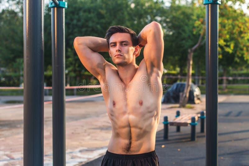 Homem de Fitnes que levanta na estação da aptidão da rua que mostra seu corpo muscular fotos de stock royalty free