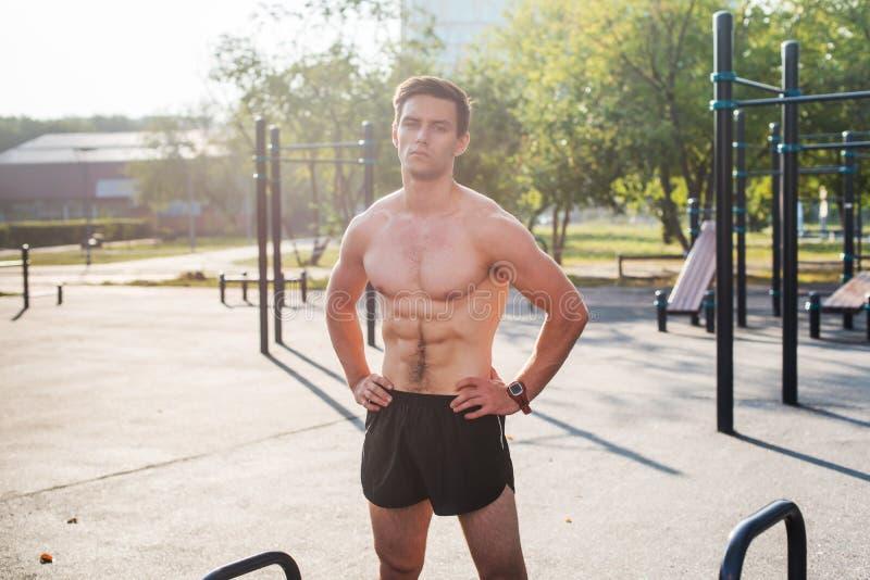 Homem de Fitnes que levanta na estação da aptidão da rua que mostra seu corpo muscular imagem de stock royalty free
