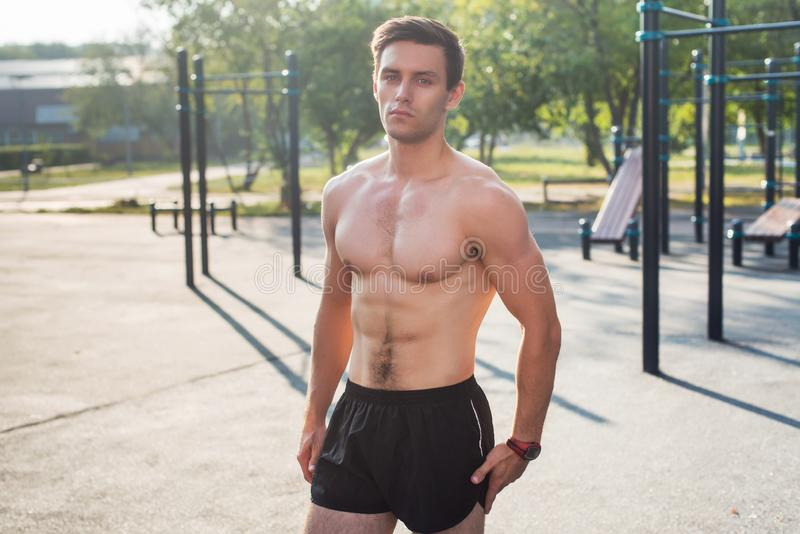 Homem de Fitnes que levanta na estação da aptidão da rua que mostra seu corpo muscular foto de stock