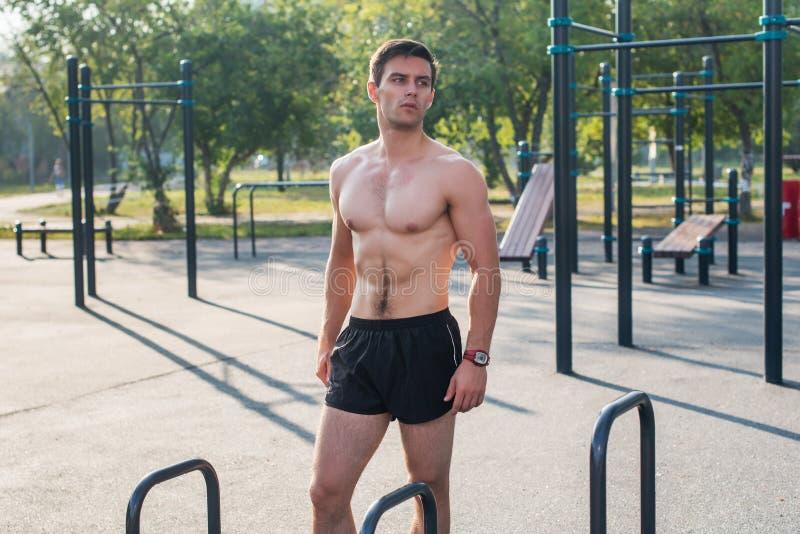 Homem de Fitnes que levanta na estação da aptidão da rua que mostra seu corpo muscular fotografia de stock