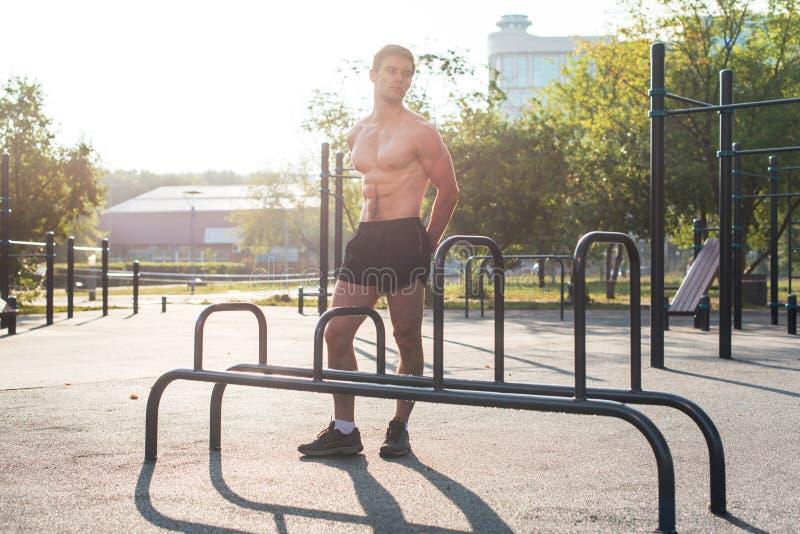 Homem de Fitnes que levanta na estação da aptidão da rua que mostra a seu corpo muscular o retrato completo do comprimento imagem de stock