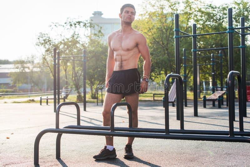 Homem de Fitnes que levanta na estação da aptidão da rua que mostra a seu corpo muscular o retrato completo do comprimento foto de stock royalty free
