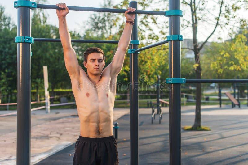 Homem de Fitnes que pendura em barras de parede Treinamento transversal do núcleo que dá certo os músculos do Abs imagens de stock