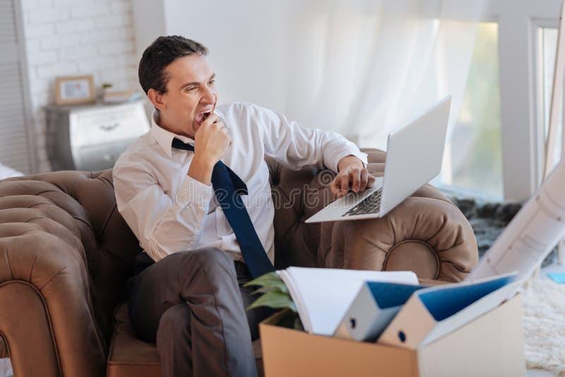 Homem de funcionamento cansado que sente sonolento ao sentar-se com um portátil foto de stock royalty free