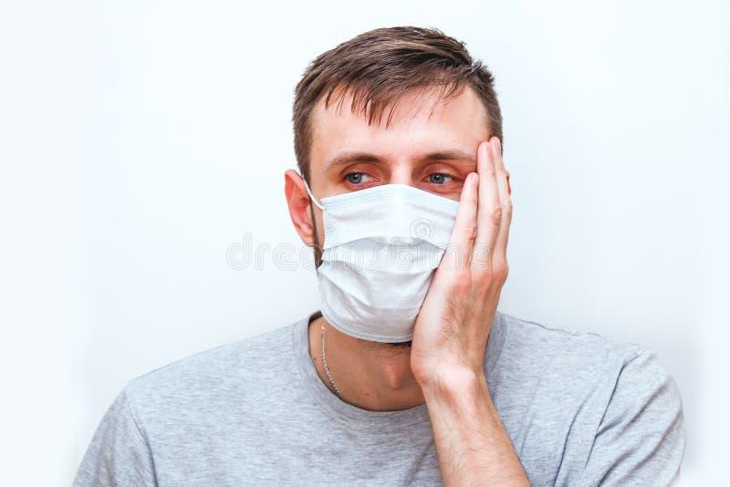 Homem de fundo branco com máscara médica no rosto, que protege contra coronavírus e outras doenças, segura seu foto de stock royalty free