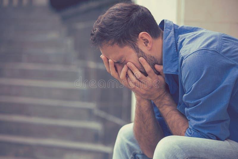 Homem de grito triste forçado que senta-se fora de guardar principal com mãos fotografia de stock