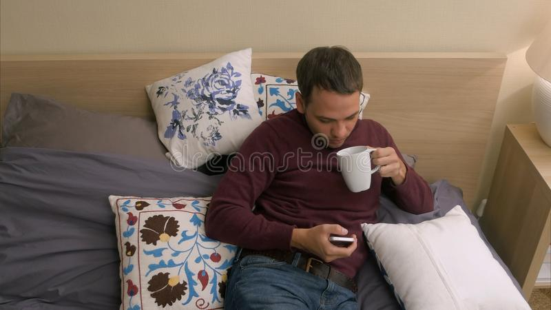 Homem de Hansome que usa o telefone esperto ao encontrar-se na cama na noite fotos de stock royalty free