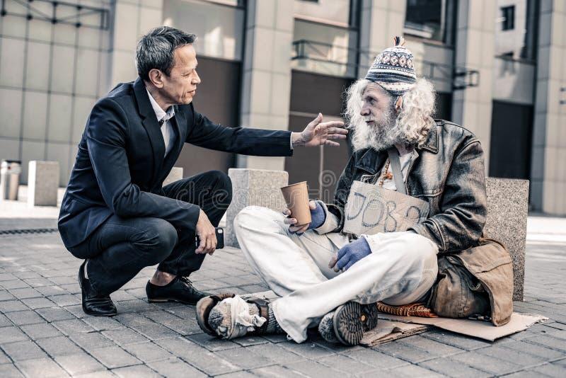 Homem de inquietação útil no traje que põe a mão sobre o ombro de sem abrigo sujos imagem de stock royalty free