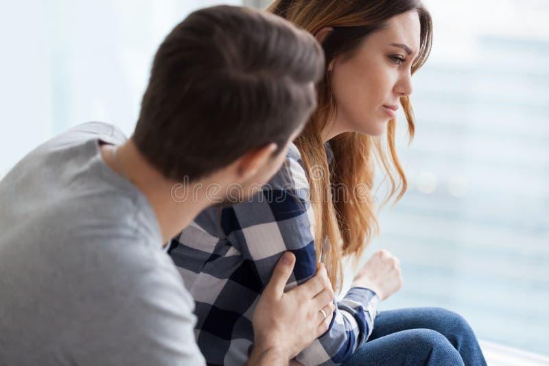 Homem de inquietação que consola a esposa virada após a luta fotografia de stock