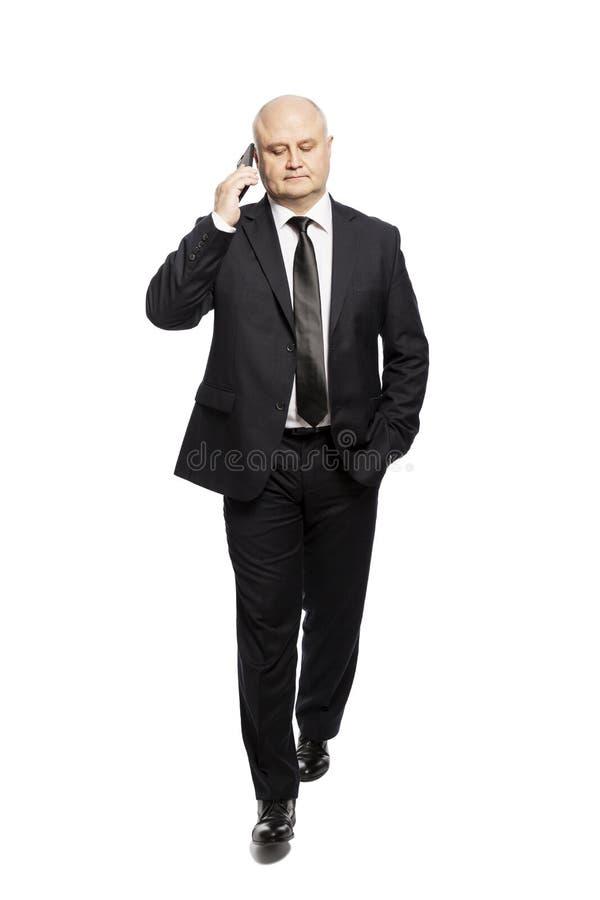 Homem de meia idade calvo de corrida em um terno com um telefone em suas mãos Homem de negócios sério Isolado no fundo branco imagem de stock