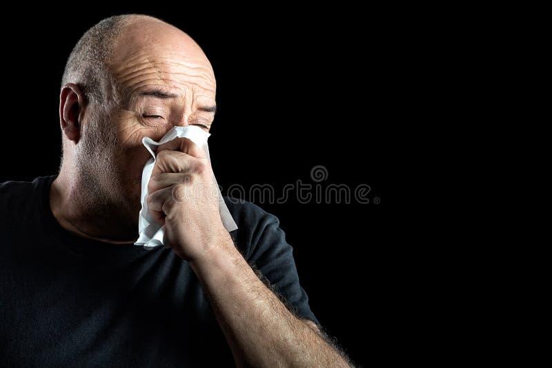 Homem de meia idade com a gripe que funde seu nariz fotografia de stock