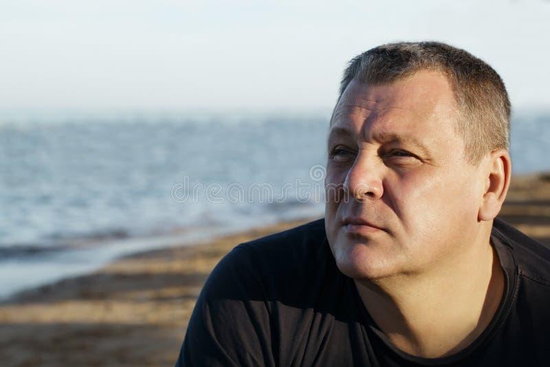 Homem de meia idade considerável que pensa na praia foto de stock