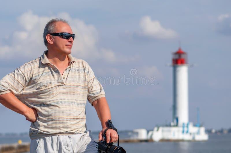 Homem de meia idade em uma camisa com uma luva curto, nos óculos de sol foto de stock