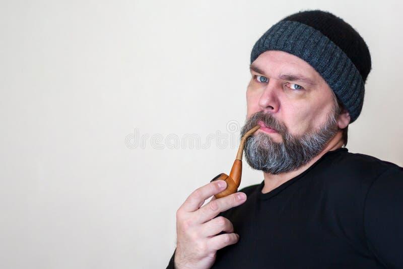 Homem de meia idade maduro s?rio com uma barba, fumando uma tubula??o, olhando a c?mera fotografia de stock royalty free