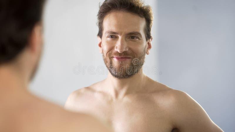 Homem de meia idade narcisístico que olha admiringly sua reflexão no espelho imagens de stock