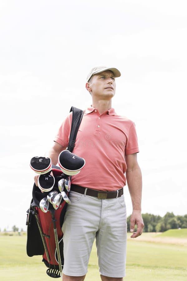 Homem de meia idade pensativo que olha ausente ao levar o saco de golfe contra o céu claro foto de stock