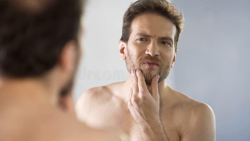 Homem de meia idade que olha criticamente sua barba no espelho, ritual da manhã fotografia de stock royalty free