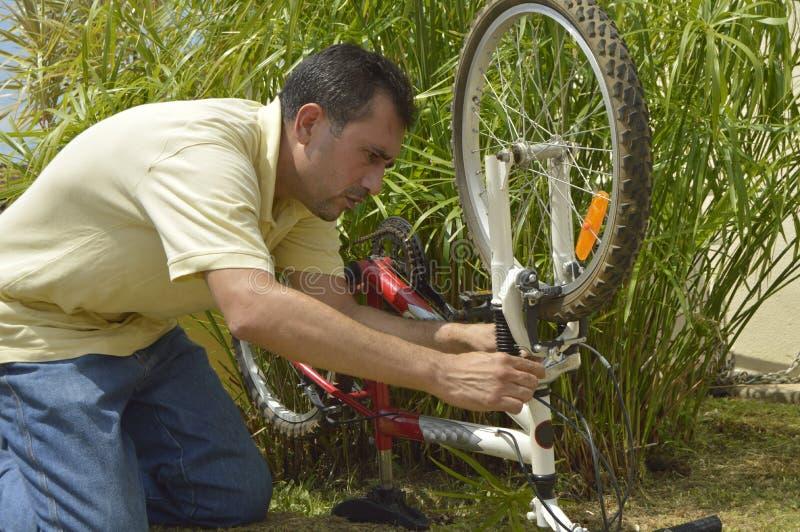 Homem de meia idade que repara uma bicicleta fotos de stock royalty free