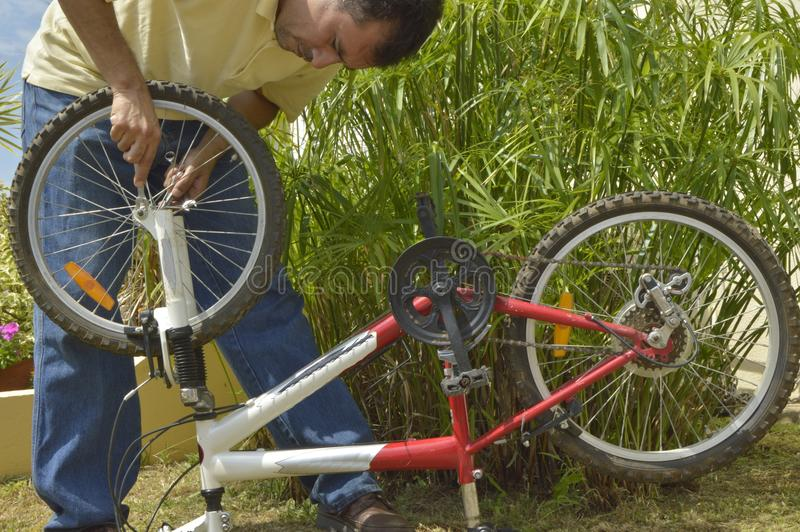 Homem de meia idade que repara uma bicicleta imagem de stock royalty free