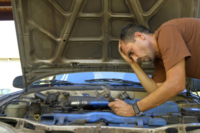 Homem de meia idade que tenta reparar seus próprios carros foto de stock