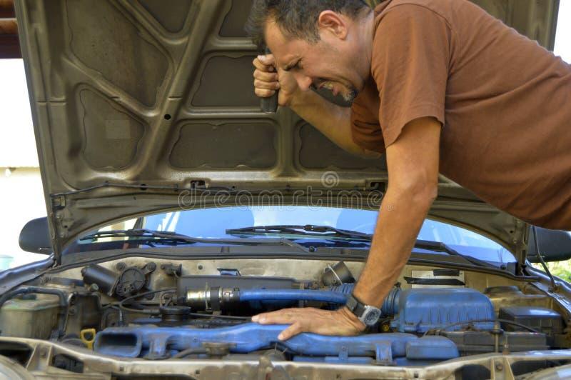 Homem de meia idade que tenta reparar seus próprios carros imagem de stock
