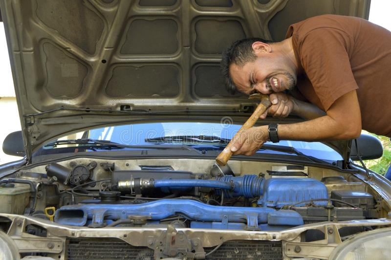 Homem de meia idade que tenta reparar seus próprios carros imagens de stock royalty free
