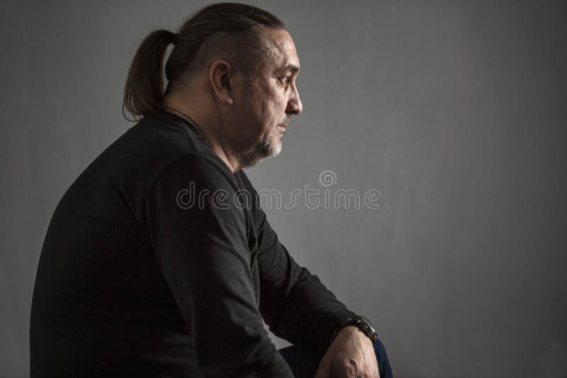 Homem de meia idade sério com cabelo longo, close-up Baixa chave imagem de stock