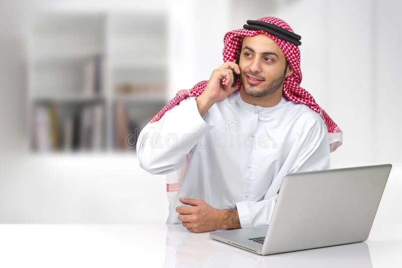 Homem de negócio árabe que fala no telefone em seu escritório fotografia de stock royalty free