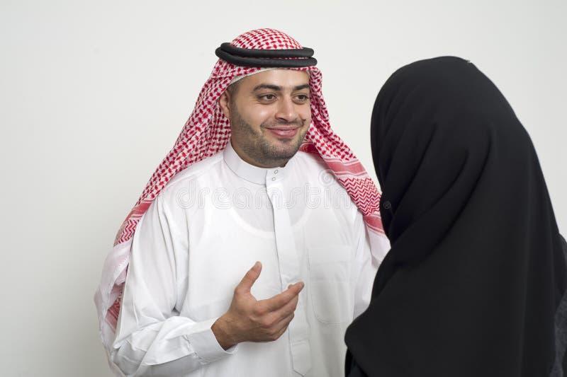 Homem de negócio árabe que tem uma discussão com uma mulher de negócios árabe no escritório fotos de stock royalty free