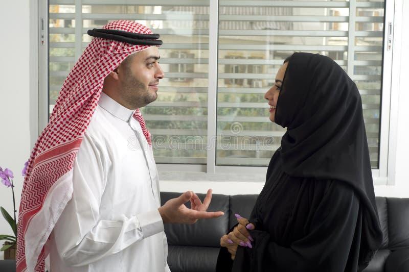 Homem de negócio árabe que tem uma discussão com uma mulher de negócios árabe no escritório imagem de stock royalty free