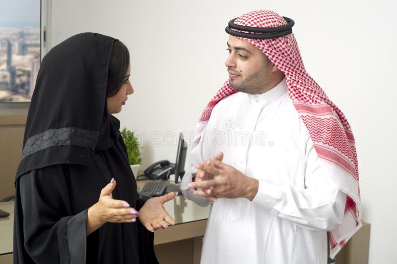Homem de negócio árabe que tem uma discussão com uma mulher de negócios árabe no escritório imagens de stock