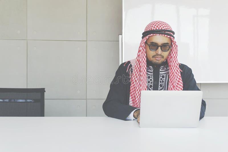 Homem de negócio árabe que trabalha no portátil foto de stock royalty free