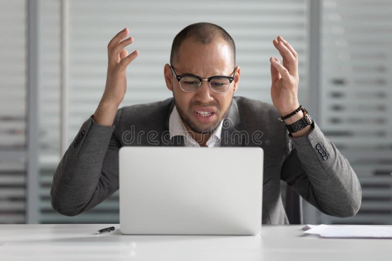 Homem de negócio africano irritado que usa o portátil louco sobre o problema do computador imagens de stock royalty free