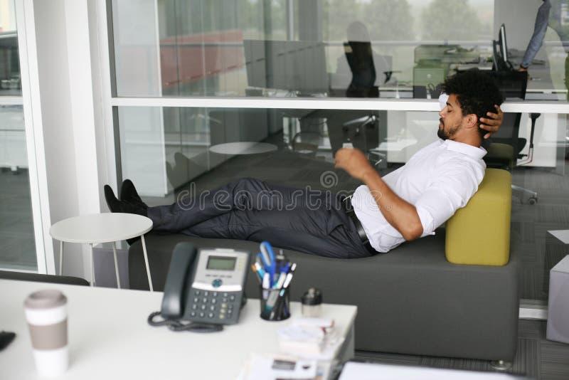 Homem de negócio africano que relaxa após o trabalho no escritório imagens de stock royalty free