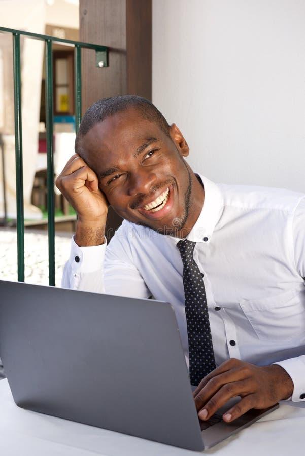 Homem de negócio afro-americano feliz que senta-se na tabela com laptop fotos de stock royalty free